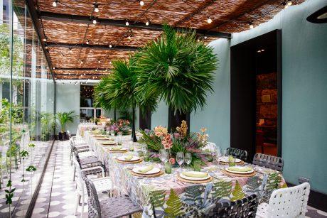 Mesa en terraza Petit Palace Santa Barbara. porche acristalado con vegetacion